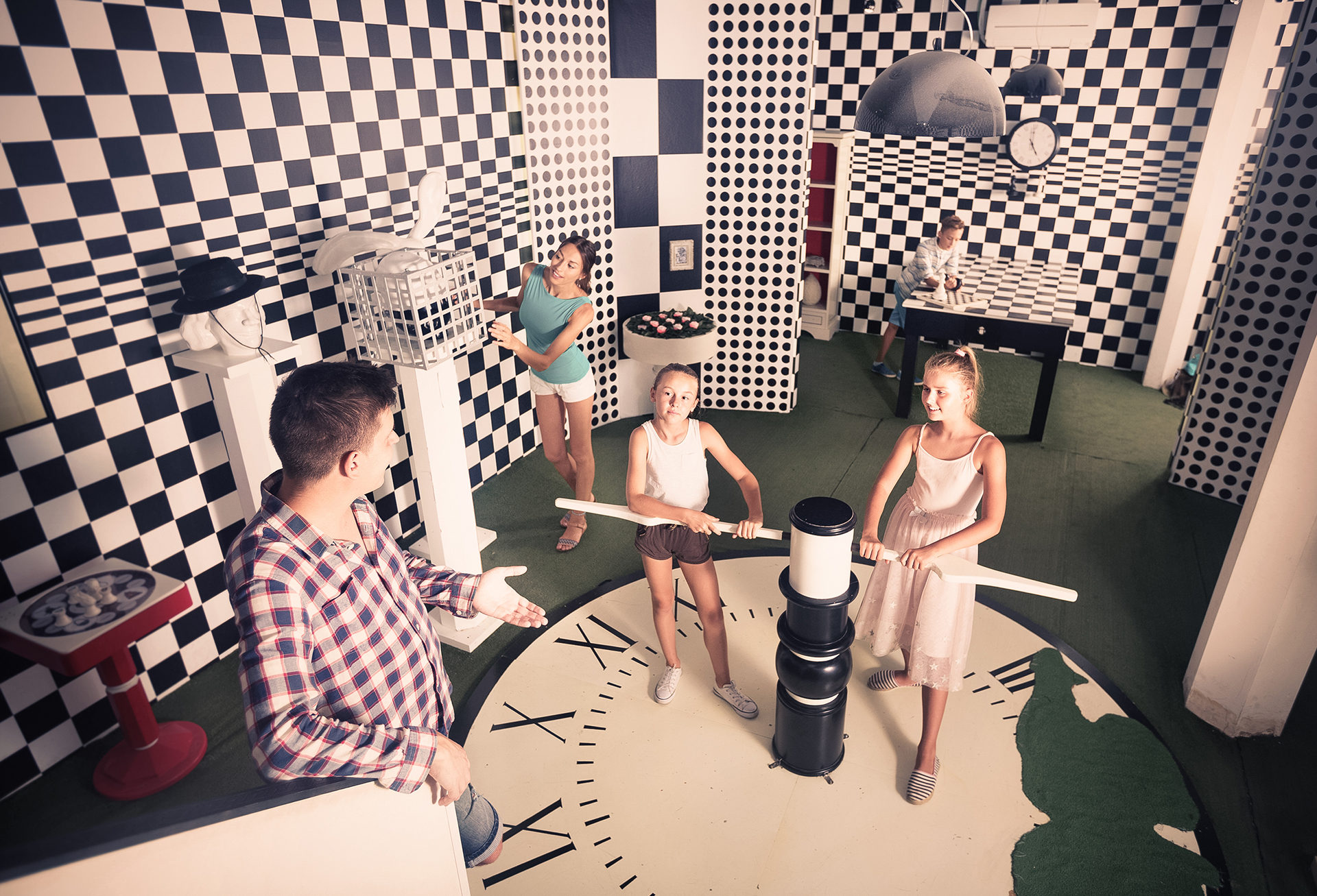 Family of five is having fun together in lost chessroom.
